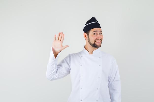 Männlicher koch winkt mit der hand zur begrüßung in weißer uniform und sieht süß aus, vorderansicht.