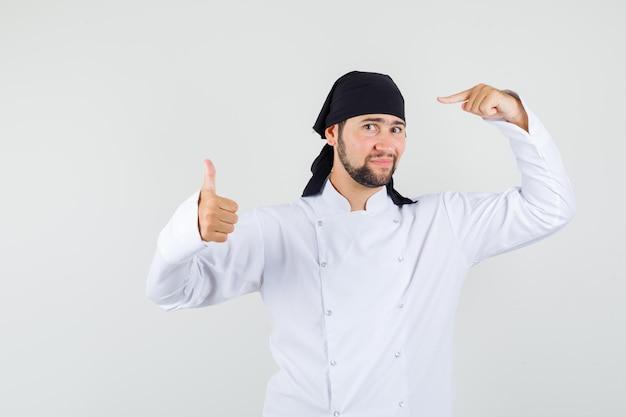 Männlicher koch zeigt auf sein halstuch mit daumen nach oben in weißer einheitlicher vorderansicht.