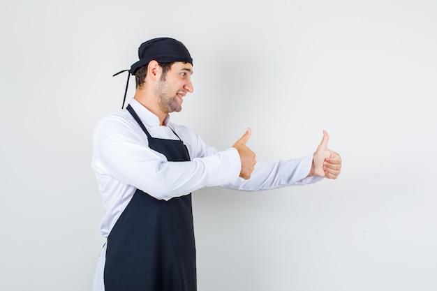 Männlicher koch zeigt daumen hoch in uniform, schürze und sieht zufrieden aus.