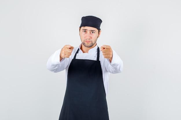 Männlicher koch zeigt finger auf sie in uniform, schürze und sieht ernst aus, vorderansicht.