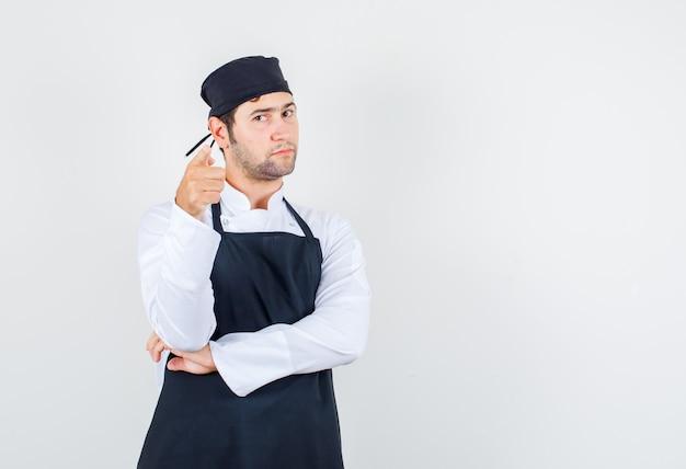 Männlicher koch zeigt finger in uniform, schürze und sieht ernst, vorderansicht.