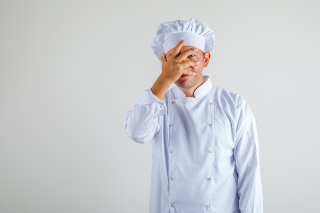 Männlicher kochkoch, der ein auge mit hand in hut und uniform bedeckt