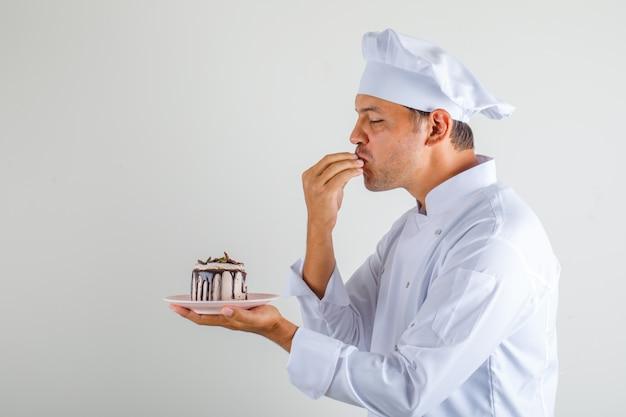 Männlicher kochkoch, der kuchen hält und leckere geste in hut und uniform macht