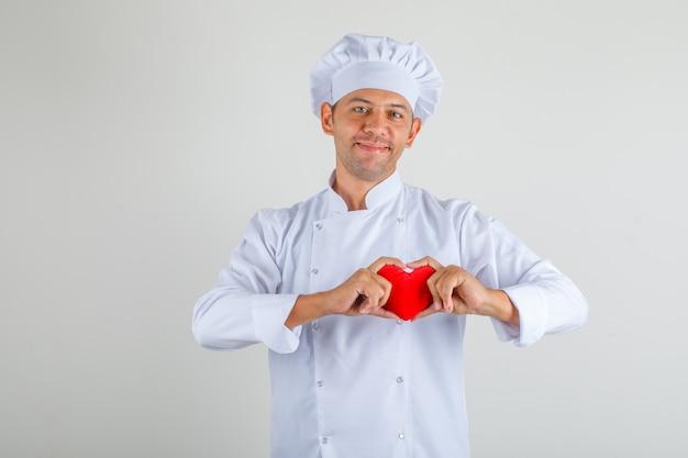 Männlicher kochkoch, der rotes herz hält und in hut und uniform lächelt und glücklich schaut