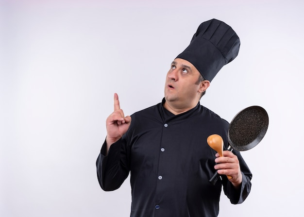 Männlicher kochkoch, der schwarze uniform trägt und kochhut hält pfanne und holzlöffel zeigt mit zeigefinger oben überrascht über weißem hintergrund