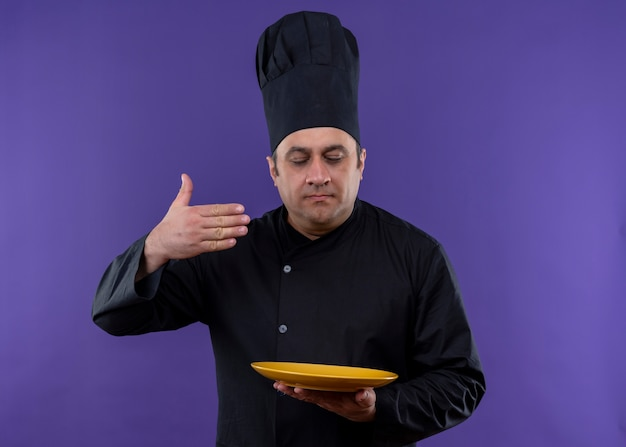 Männlicher kochkoch, der schwarze uniform und kochhut hält, der bratpfanne hält, der angenehmen geruch von leckerem essen über lila hintergrund steht