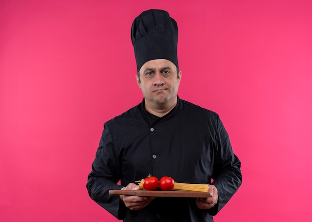 Männlicher kochkoch, der schwarze uniform und kochhut hält, der hölzernes schneidebrett mit tomaten betrachtet, die kamera mit ernstem gesicht betrachten, das über rosa hintergrund steht