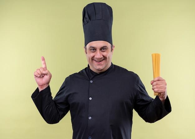 Männlicher kochkoch, der schwarze uniform und kochhut hält, der reihe-spaghetti hält, die mit dem finger nach oben zeigen, die kamera lächelnd liebenswert über grünem hintergrund stehend