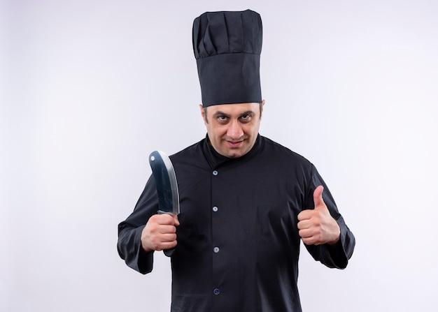 Männlicher kochkoch, der schwarze uniform und kochhut hält, der scharfes küchenmesser lächelnd zeigt daumen hoch stehend über weißem hintergrund