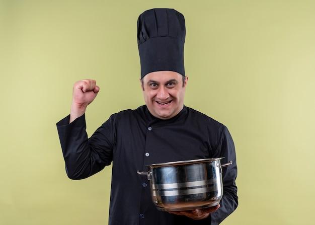 Männlicher kochkoch, der schwarze uniform und kochhut hält, der topf hält, der kamera betrachtet, die glückliche und aufgeregte geballte faust über grünem hintergrund lächelt