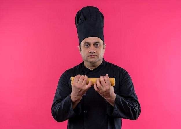 Männlicher kochkoch, der schwarze uniform und kochhut hält, die rohe spaghretti halten, die kamera mit ernsthaftem gesicht betrachten, das über rosa hintergrund steht
