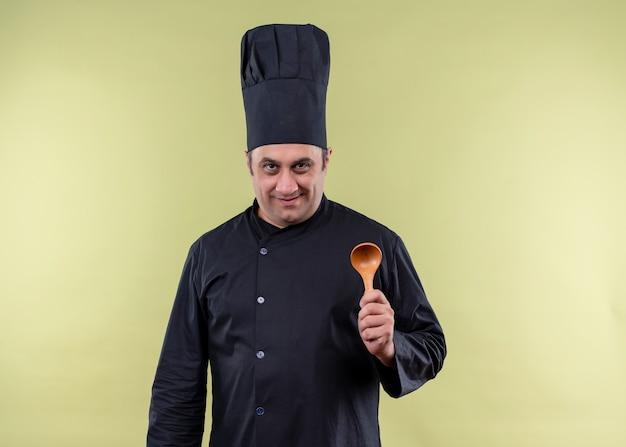 Männlicher kochkoch, der schwarze uniform und kochhut trägt, der hölzernen löffel zeigt kamera mit lächeln auf gesicht steht über grünem hintergrund