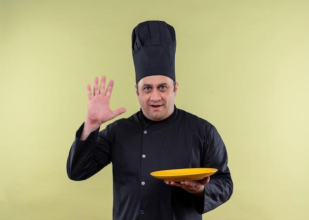 Männlicher kochkoch, der schwarze uniform und kochhut trägt, die einen leeren teller hält, der arm nummer fünf zeigt, der über grünem hintergrund steht