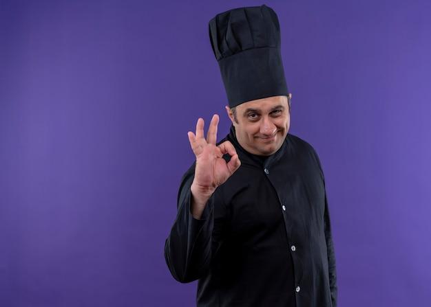 Männlicher kochkoch, der schwarze uniform und kochhut trägt, die kamera lächelnd zeigt, ok zeichen zeigend, das über lila hintergrund steht