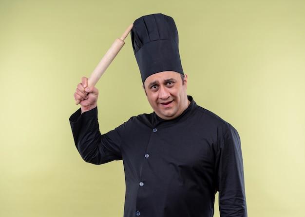 Männlicher kochkoch, der schwarze uniform und kochhut trägt, kratzt seinen kopf mit rooling pin, der verwirrt steht über grünem hintergrund