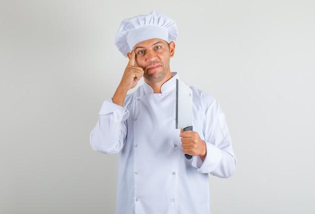 Männlicher kochkoch hält messer für fleisch und denkt in uniform und hut und sieht positiv aus
