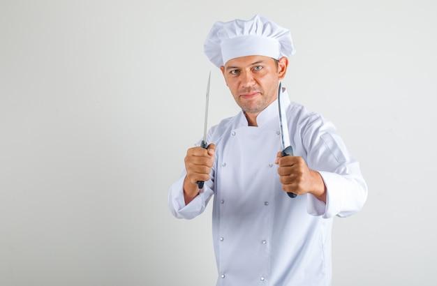 Männlicher kochkoch hält metallmesser in uniform und hut und sieht selbstbewusst aus