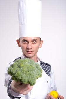 Männlicher kochkochmann im weißen uniformhemd, das lokalisiert auf weißem wandstudioporträt aufwirft. koch-food-konzept. kopieren sie den speicherplatz. brokkoli und eine zitrone in den händen des kochs nahaufnahme auf einem weiß