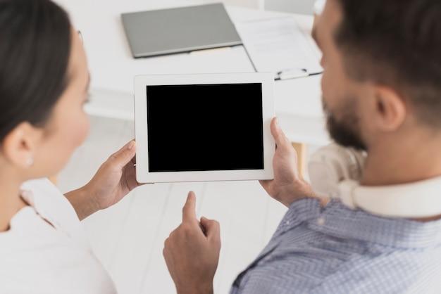 Männlicher kollege, der dem weiblichen kollegen tablette zeigt