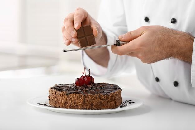 Männlicher konditor, der leckeren schokoladenkuchen in der küche verziert