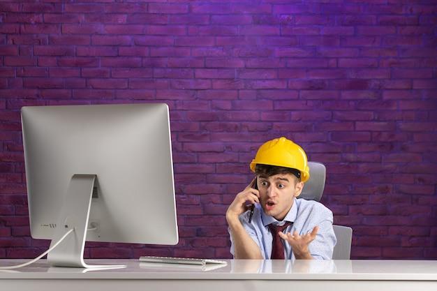 Männlicher konstrukteur der vorderansicht hinter dem schreibtisch, der am telefon spricht
