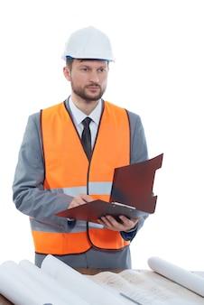 Männlicher konstruktionsvorarbeiter in einer sicherheitsweste und einem wegschauenden helm