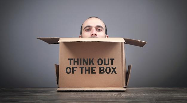 Männlicher kopf, der aus einem karton herauskommt. denke mal kreativ