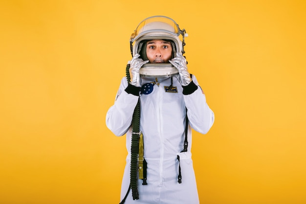 Männlicher kosmonaut in raumanzug und helm, der seinen helm mit seinen händen mit überraschender geste an der gelben wand hält.