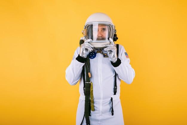 Männlicher kosmonaut in raumanzug und helm, helm mit beschlagenem glas haltend, auf gelber wand.