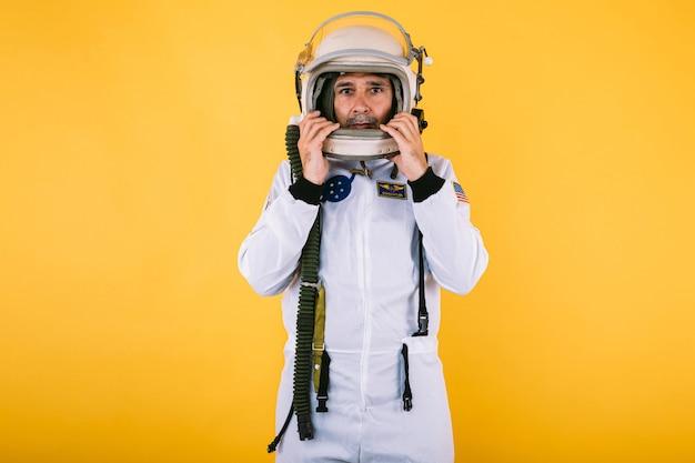 Männlicher kosmonaut in raumanzug und helm, helm mit händen haltend, auf gelber wand.