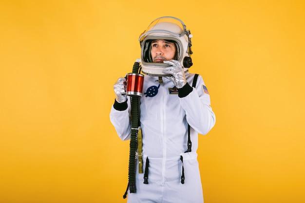 Männlicher kosmonaut in raumanzug und helm mit einer tasse kaffee in seinen händen, auf gelber wand.
