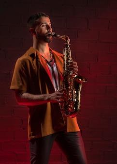 Männlicher künstler, der das saxophon spielt