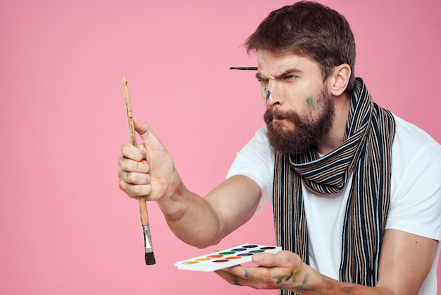 Männlicher künstler malt ein bild auf leinwand mit einer staffelei