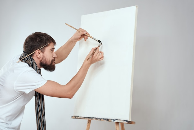 Männlicher künstlerpinsel in den händen des staffelei-kunsthobby-lichtschals um seinen hals.