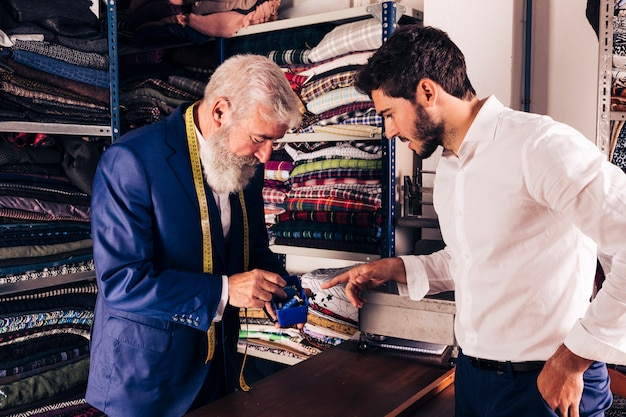 Männlicher kunde, der garnrolle mit männlichem modedesigner in seinem shop vorwählt