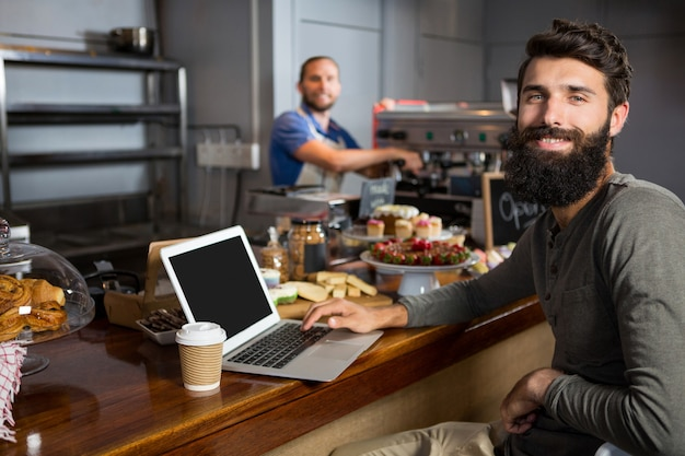 Männlicher kunde, der laptop beim kaffee am schalter im kaffeehaus verwendet