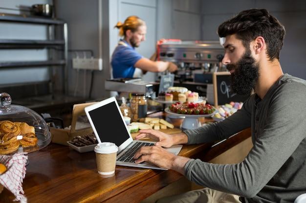 Männlicher kunde, der laptop beim kaffee am schalter verwendet