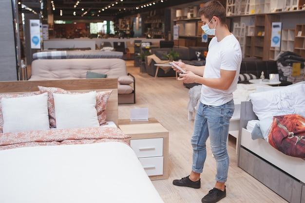 Männlicher kunde, der medizinische gesichtsmaskeneinkäufe für möbel trägt