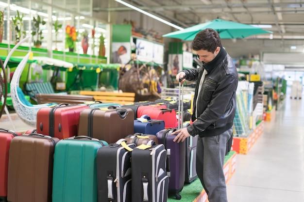 Männlicher kunde, der reisekoffer im supermarkt wählt. er hält den griff