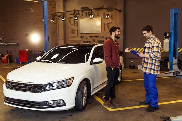 Männlicher kunde im auto-service-center, der dem mechaniker mit zwischenablage die probleme seines autos erklärt