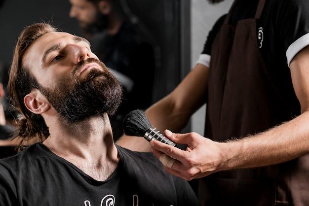 Männlicher kunde mit dem bart nahe dem friseur, der rasierpinsel hält