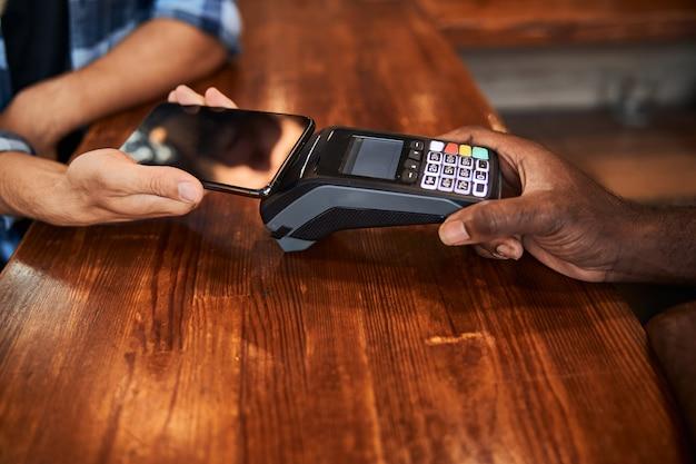 Männlicher kunde mit mobiltelefon für kontaktloses bezahlen