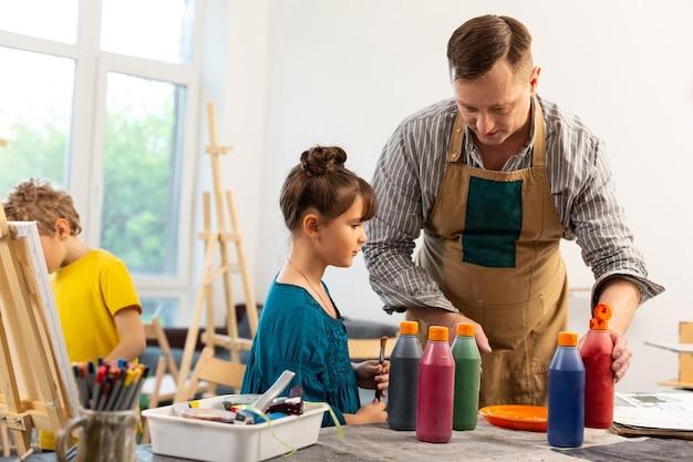 Männlicher kunstlehrer, der niedliches kleines mädchen mit bunten farben hilft