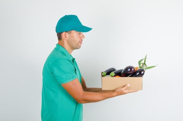 Männlicher kurier, der gemüse im kasten im grünen t-shirt mit kappe liefert.