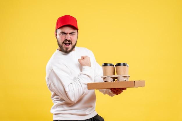 Männlicher kurier, der lieferung lebensmittelbox und kaffee auf gelb hält holding