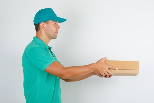 Männlicher kurier, der pappkarton im grünen t-shirt mit kappe liefert und fröhlich schaut.
