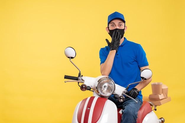 Männlicher kurier der vorderansicht, der auf dem fahrrad in der maske auf gelber pandemie-lieferjob-covid-arbeitsuniform sitzt