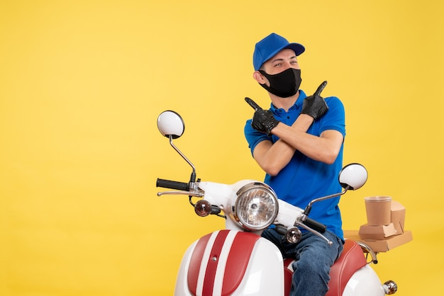 Männlicher kurier der vorderansicht, der auf fahrrad in der maske auf gelbem dienstpandemie-lieferkovid-arbeitsuniformjob sitzt