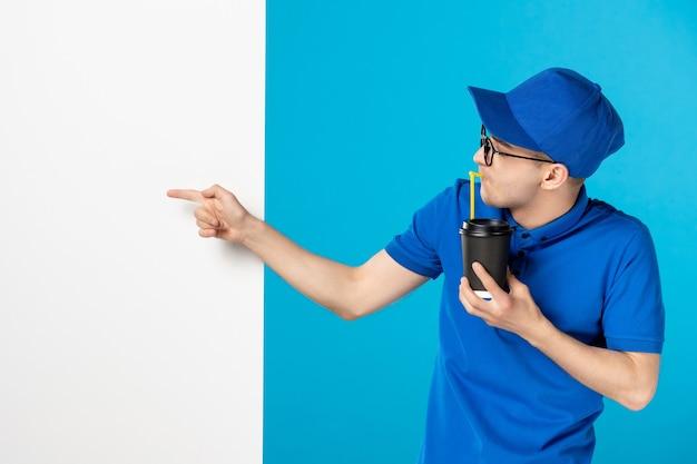Männlicher kurier der vorderansicht, der kaffee auf einem blau trinkt