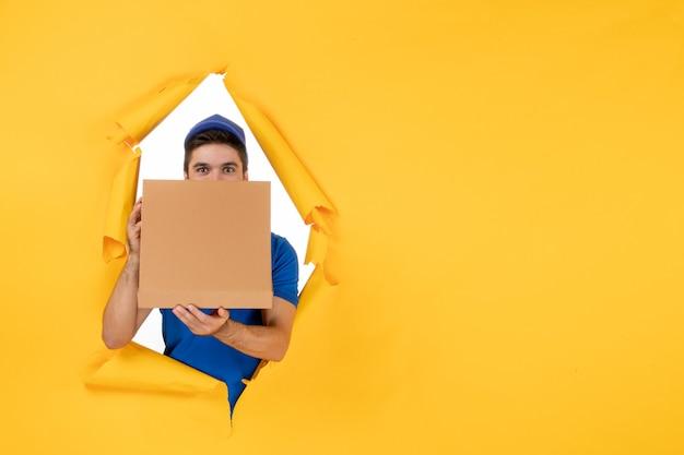Männlicher kurier der vorderansicht, der pizzakarton auf gelbem raum hält